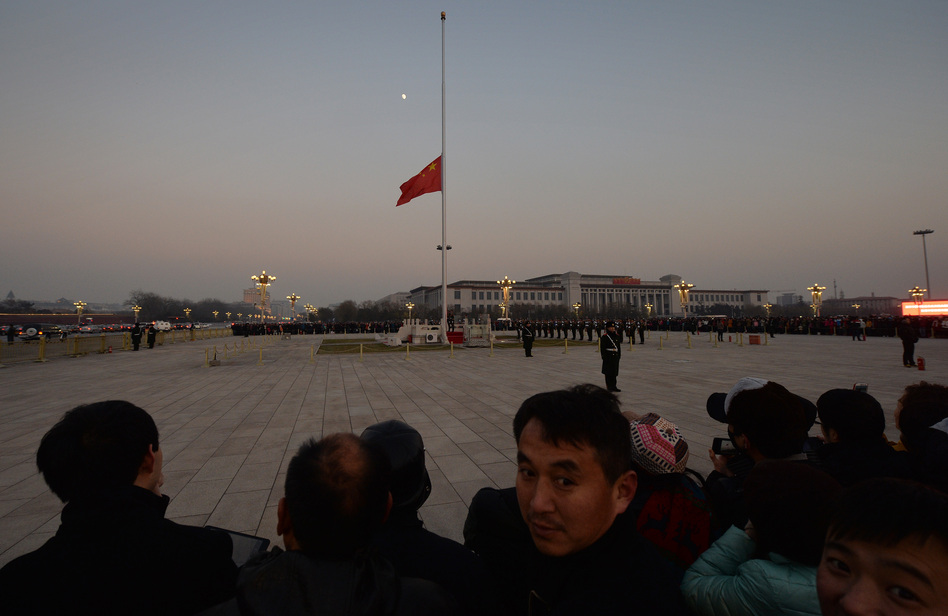 The Chinese flag is seen in front of a view of the moon at Beijing's Tiananmen Square in December, when China's first moon rover touched the lunar surface. That feat was widely celebrated — but observers believe the rover has now run into serious trouble. (Mark Ralston/AFP/Getty Images)
