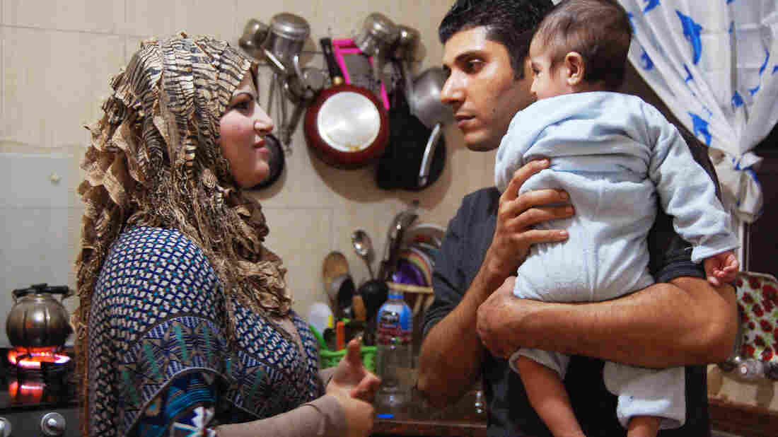 """Ala'a Miqbel (shown here with his wife and their youngest son in their Gaza City apartment) was held for nearly four weeks in an Israeli prison, then released without charges. There, he met the """"sparrows"""" — Palestinians who appear to be fellow prisoners but are actually gathering information for the Israelis."""
