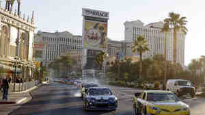 Las Vegas may reach new record highs on Wednesday and Thursday, with temperatures in the low 70s predicted. Here, NASCAR racecars drive through the city during an event last month.