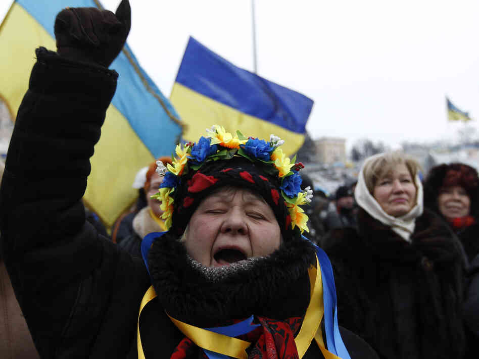 Anti-government protesters wave flags and shout slogans Tuesday in Kiev, Ukraine.