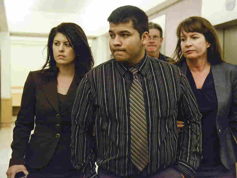 Erick Munoz, flanked by lawyers, walks to 96th District Court last Friday. A judge ordered a Texas hospital to remove life support from his wife, Marlise.