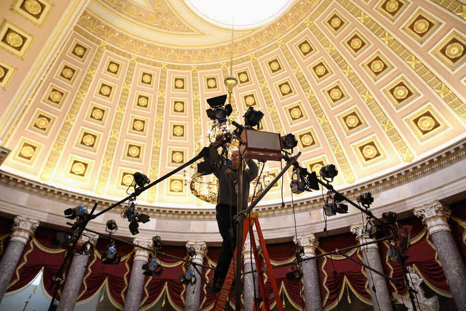 Television lighting technicians build sets inside Statuary Hall for post-speech interviews.