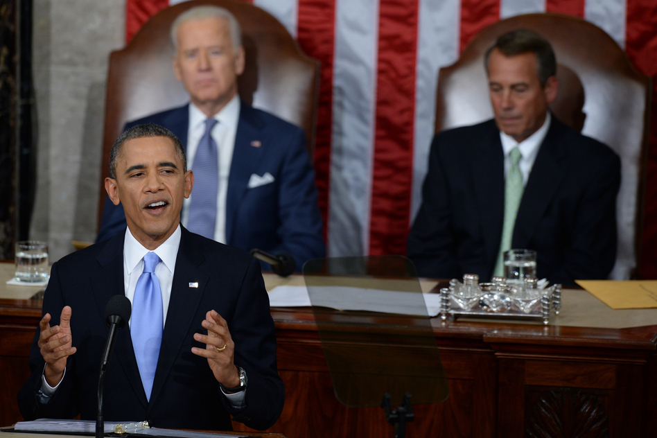 With Vice President Biden and House Speaker John Boehner, R-Ohio, seated behind him, Obama called on Congress to pass immigration reform. (AFP/Getty Images)
