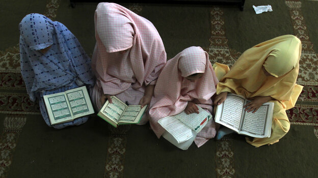 Palestinian girls read the Koran at a camp in Gaza City, June 2012. In poor countries, boys are 20 percent more likely than girls to enroll in school, UNICEF says.