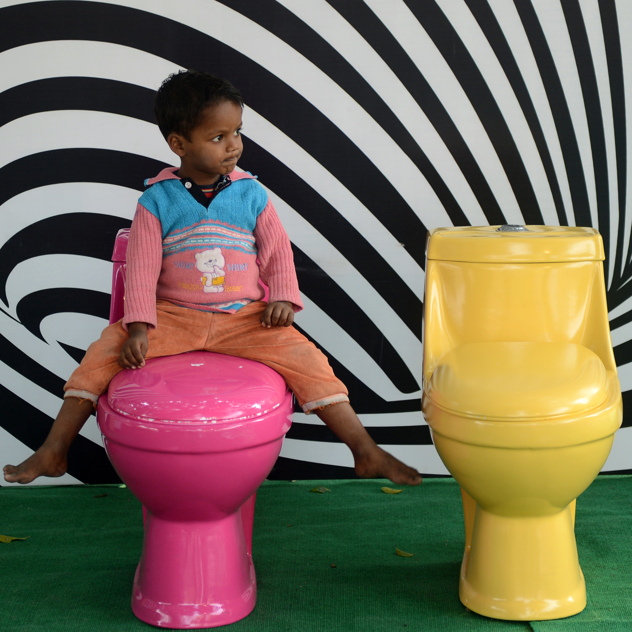 An Indian child plays on toilets during a sanitation campaign in New Delhi, November 2012. More than 130 million Indian households still have no clean latrines.