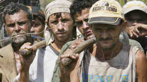Brazilian slave laborers stop their work to listen to a Labor Ministry inspector explain their legal rights, on the Bom Jesus farm in the Amazon basin in 2003.
