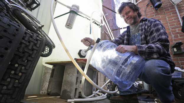 Jonathan Steele, owner of Bluegrass Kitchen, fills a jug with bottled water from a tank he installed in the back of his Charleston restaurant. (AP)