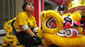 Gund Kwok troupe member Heang Ly takes a break next to her lion costume during a rehearsal in Boston's Chinatown.