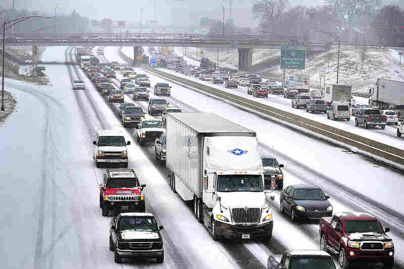 A winter storm dumps snow in central and southern Alabama on Tuesday as traffic crawls along I-20/59 near downtown Birmingham.