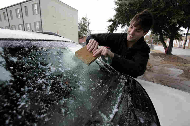 Cory Baker scrapes ice off of his windshield with a block of wood in Mobile, Ala.