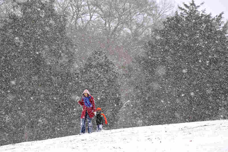 Andrea Coleman and Lennon Davis walk in Orr Park in Montevallo, Ala. The storm left more ice and snow than expected in parts of Alabama and Georgia.