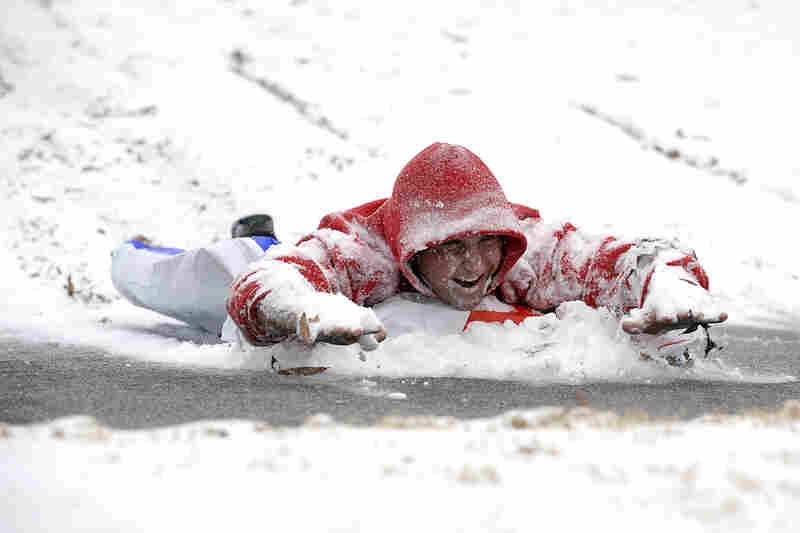 Cooper Gouge slides down a hill at Piedmont Park in Atlanta.
