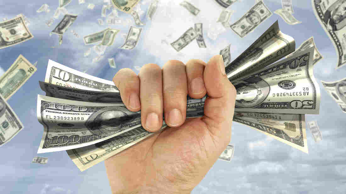 A hand grabs a wad of money against a background of money falling from the sky.