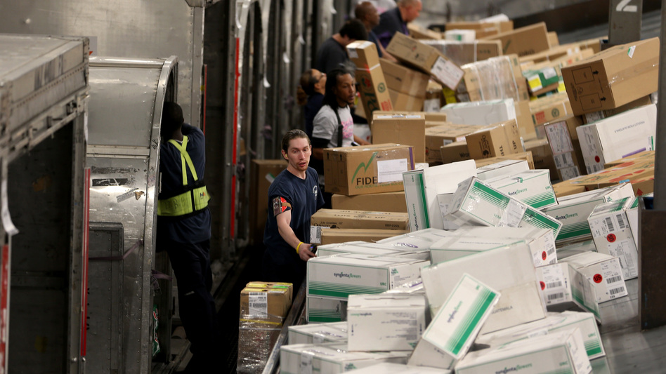 "FedEx employees sorted through mounds of packages in December at one of the company's facilities in Miami. Consumer spending helped fuel the economy in the third quarter. Gross domestic product grew at a 3.2 percent annual rate (a figure that adjusts for holiday spending to show the ""real"" growth). (Getty Images)"