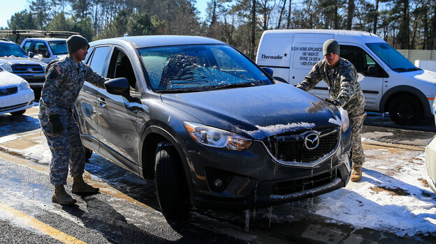 Staff Sgt. Anthony Orsi, left, and Staff Sgt. Raymond Novak of the Army National Guard helped Lauren Gates (in vehicle) retrieve her car Thursday from the Cumberland Boulevard exit ramp along I-75 North in Atlanta. Guard members and police were working to reunite drivers with more than 2,000 cars.