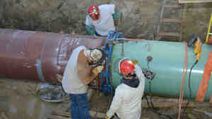 Pipefitters work on construction of the Keystone XL Pipeline's southern portion outside Tulsa, Okla., last January.