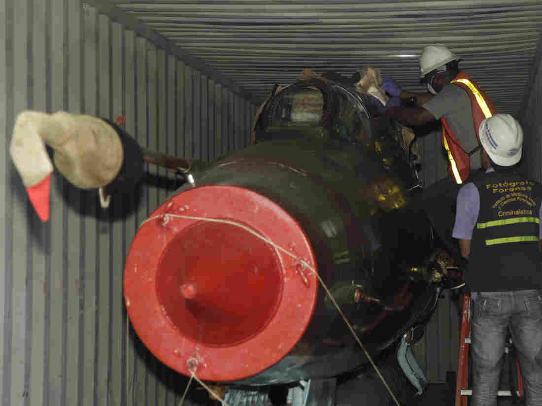 Investigative officers look inside a container carrying a Russian-made MIG-21 fighter jet aboard the Chong Chon Gang, in the port city of Colon, Panama, in July.