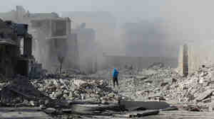A Syrian man walks through debris following an alleged air strike by Syrian government forces on Fr