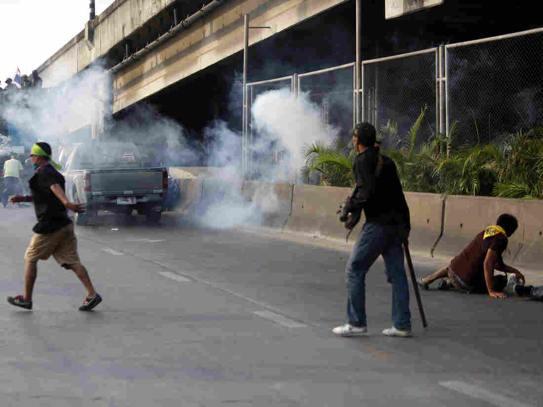 Anti-government protesters run as an explosion takes place near their vehicle during a gunfight between supporters and opponents of Thailand's government near Laksi district office in Bangkok on Saturday.
