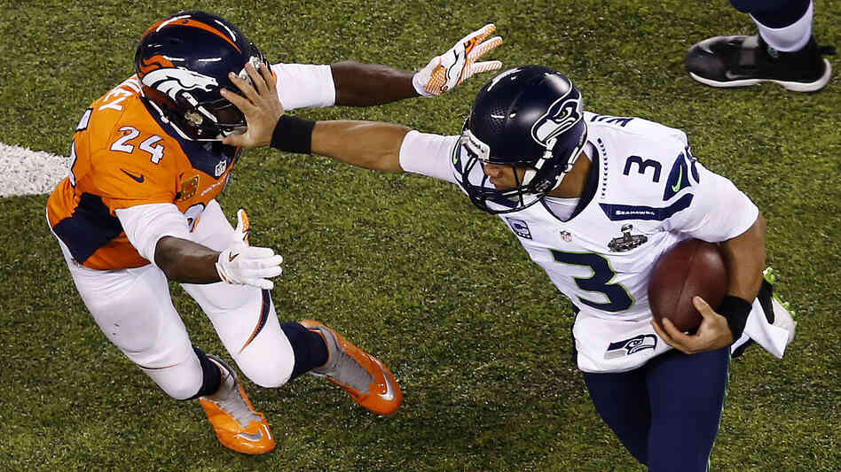 Seahawks quarterback Russell Wilson stiff-arms Broncos cornerback Champ Bailey on Sunday during Super Bowl XLVIII at MetLi