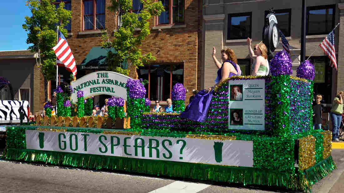 The 2011 Asparagus Queen, Megan Roskan, and runner-up Christine Merten wave to spectators during an Independence Day parade in Whitehall, Mich. With interests waning in agricultural pageants, organizers are relaxing the requirements to encourage more people to apply.