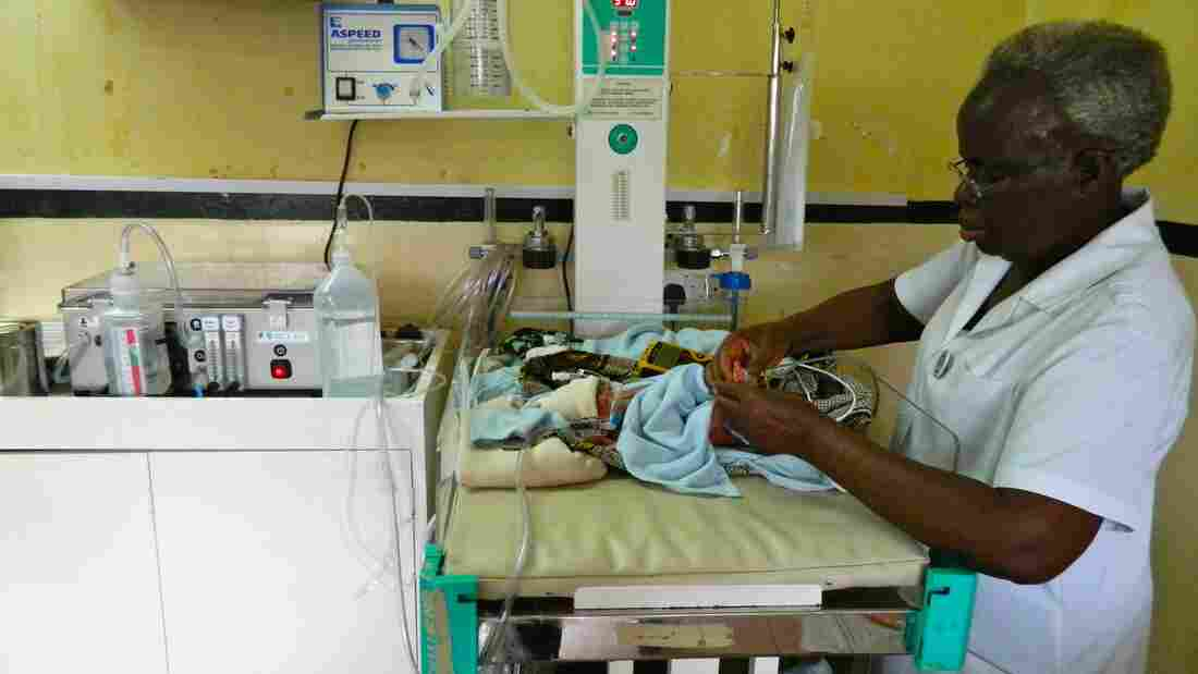 A nurse attaches the low-cost breathing machine (far left) to an infant at The Queen Elizabeth Central Hospital in Blantyre, Malawi.
