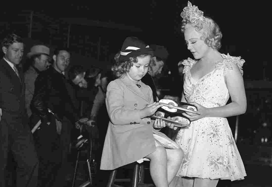 Skater Sonja Henie (right) presents Shirley Temple with a pair of skates.