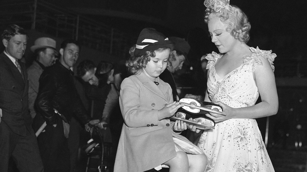 Skater Sonja Henie (right) presents Shirley Temple with a pair of skates. (AP)