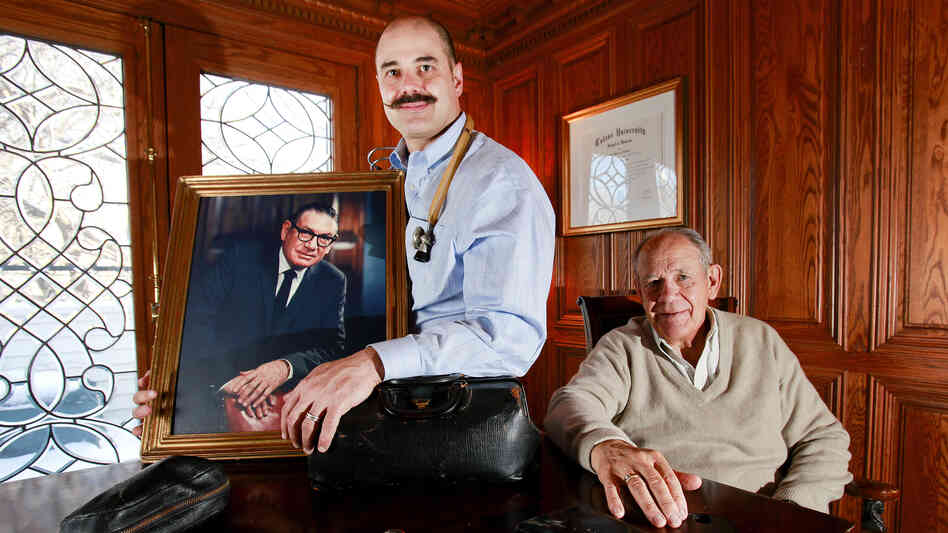 Michael Sawyer, the latest doctor in his family, holds a portrait of his grandfather Dr. Ken Sawyer, while his father Robert, a surgeon, looks on.