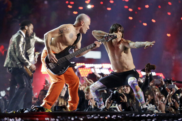 The Red Hot Chili Peppers band members Flea, center, and Anthony Kiedis perform during the halftime show of the S