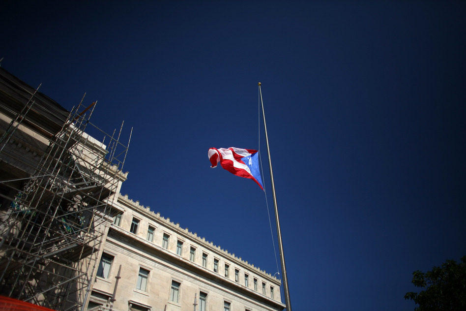 The Puerto Rican flag waves in front of the south wing of the Capitol in San Juan, Puerto Rico. (Ricardo Arduengo/AP)
