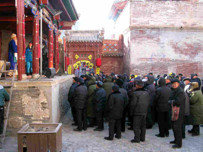 Tourists and locals enter a courtyard to watch a Chinese New Year's opera performance in Nuanquan Town in northern Hebei province.