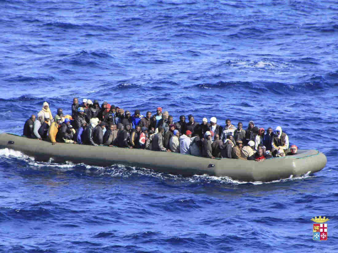 Migrants are seen in a boat during a rescue operation by Italian navy ship San Marco off the coast to the south of the Italian island of Sicily on Wednesday.