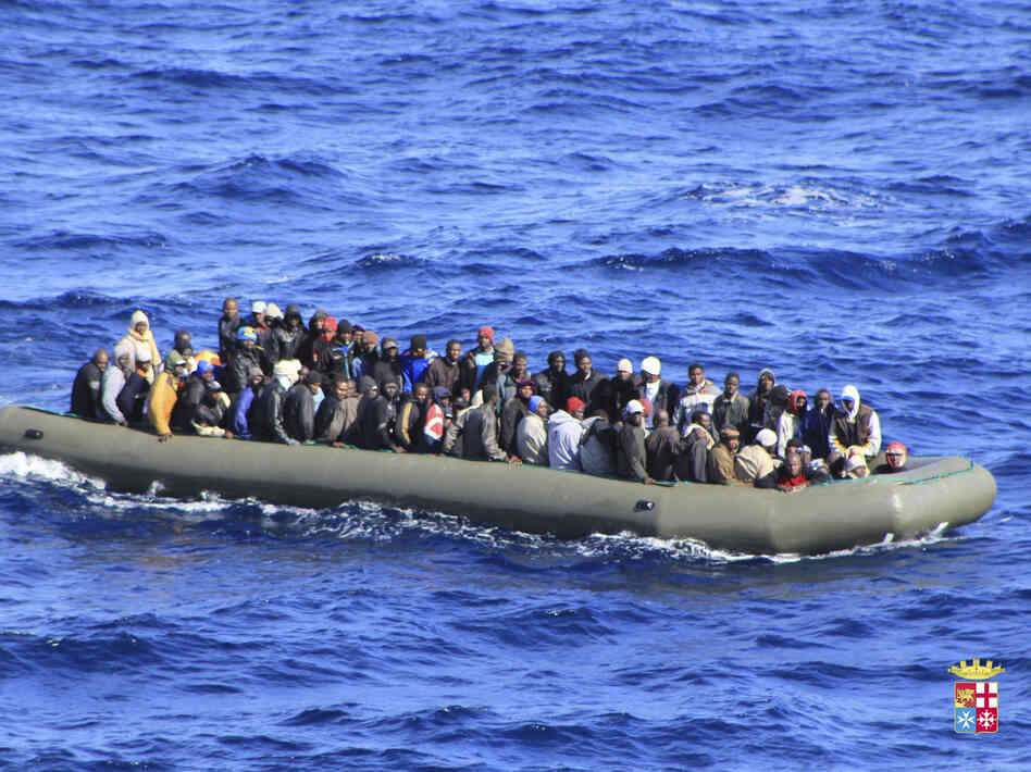 Migrants are seen in a boat during a rescue operation by Italian navy ship San Ma