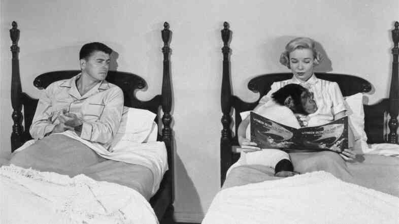 Ronald Reagan, portraying a chimpanzee-raising professor, is shown with Diana Lynn in a scene from the 1951 film Bedtime for Bonzo.