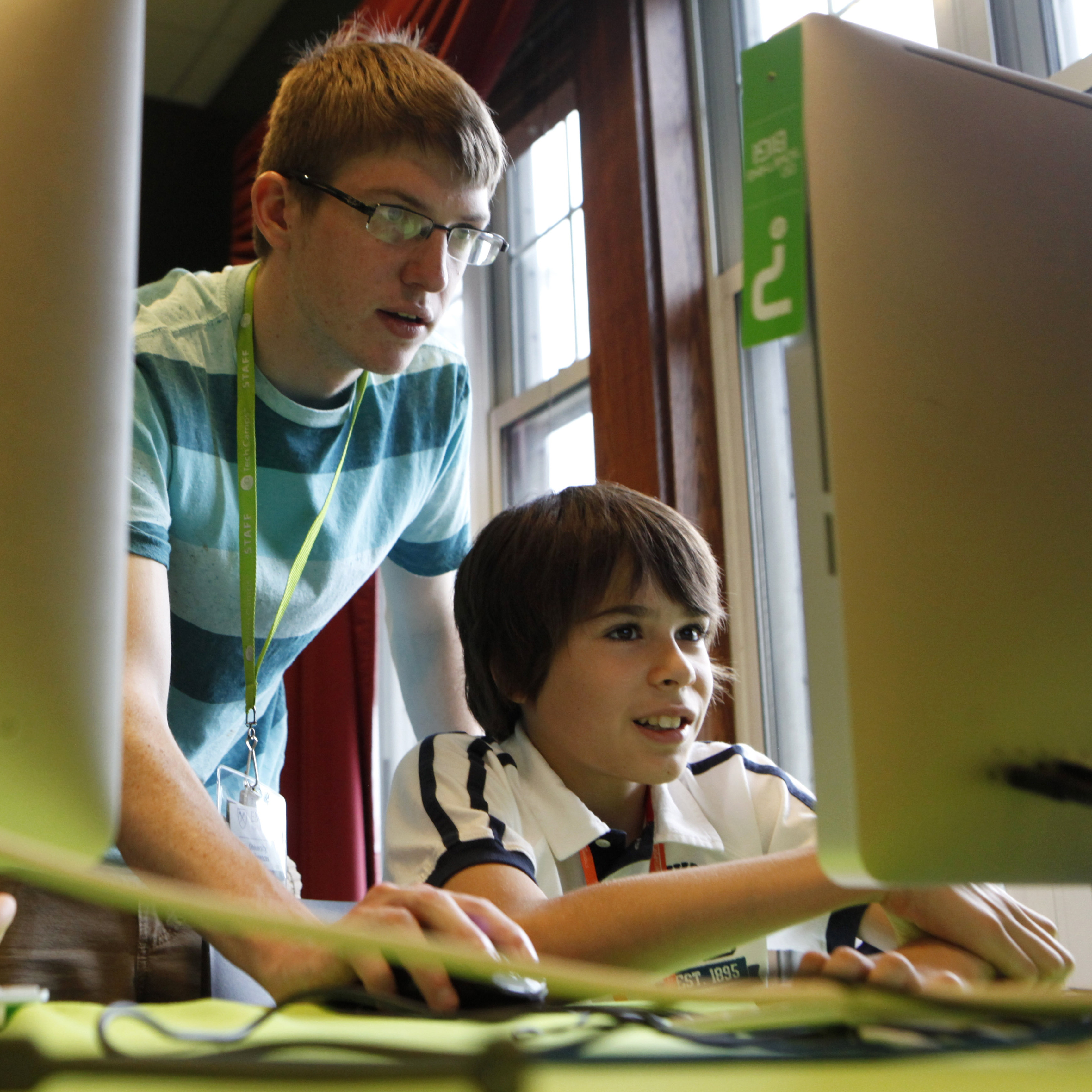 An instructor helps a young camper create a video game at a tech camp in Atlanta for kids to learn how to code.