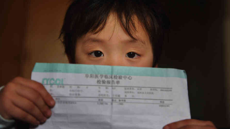 A girl with hepatitis C holds a medical report while being treated at a hospital in Hefei, China, in 2011. China has one of the greatest burdens of hepatitis C, but it's still not clear whether a deal for lower prices for a new drug from Gilead Sciences will apply there.
