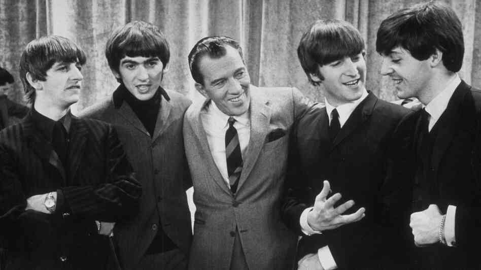 Ed Sullivan smiles while standing with The Beatles on the set of his variety show on Feb. 9, 1964.