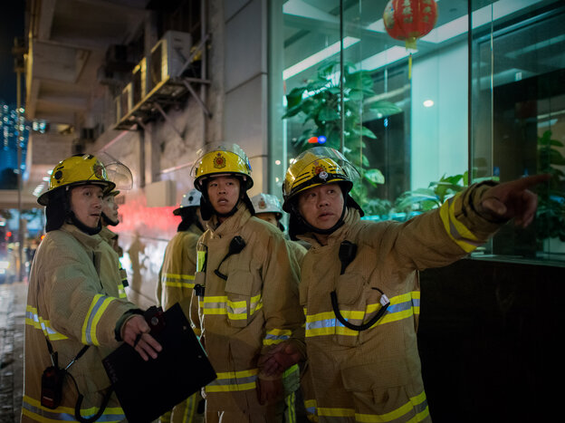 Firemen are seen near the site where a World War II-era bomb weighing a ton was discovered in Hong Kong on Thursday.