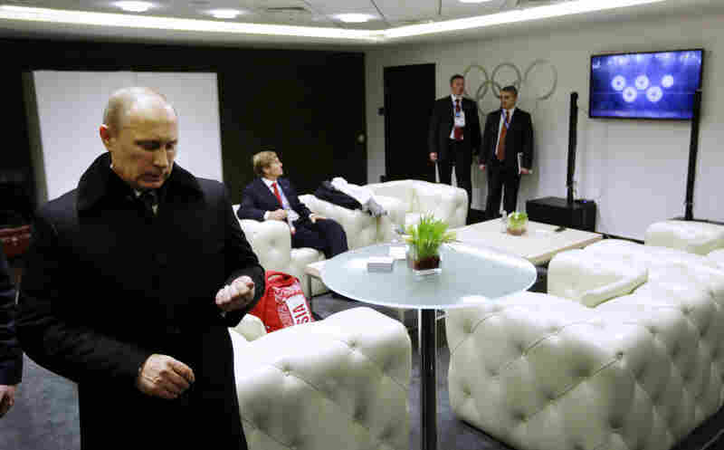 Russian President Vladimir Putin waits to be introduced, as a television screen displays the snowflakes transforming into the Olympic rings.