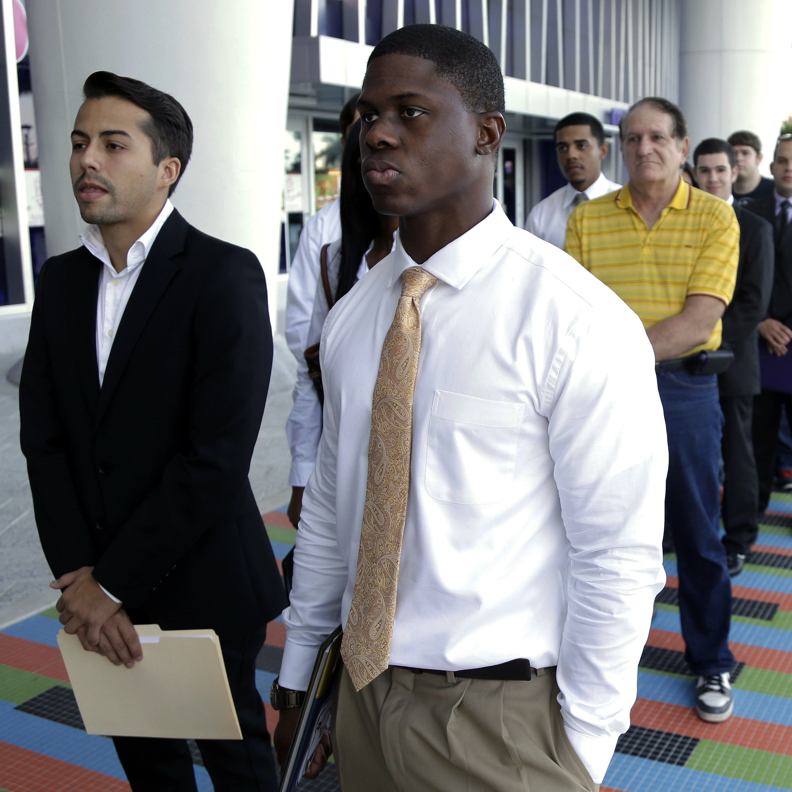Luis Mendez, 23 (left), and Maurice Mike, 23, wait in line at a job fair held by the Miami Marlins at Marlins Park on Oct. 23, 2013. The nation's unemployment rate slipped to 6.6 percent in January, but employers added only 113,000 jobs to their payrolls last month, the Bureau of Labor Statistics reported Friday.