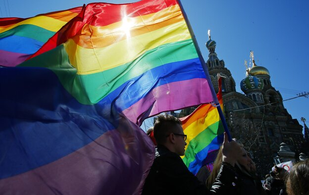 Gay rights activists carry rainbow flags as they march during a May Day rally in St. Petersburg, Ru