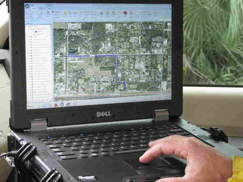 Chris Wasil, a forest area supervisor for Palm Beach County, demonstrates how satellite maps depict the location and movement of fire equipment.
