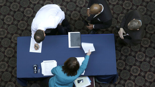 Job seekers sign in before meeting prospective employers during a career fair at a hotel in Dallas last month.