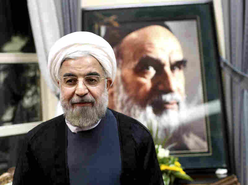 Rouhani (then president-elect), stands in front of a portrait of the late revolutionary founder Ayatollah Khomeini, during a visit to his shrine just outside Tehran, on June 16, 2013.