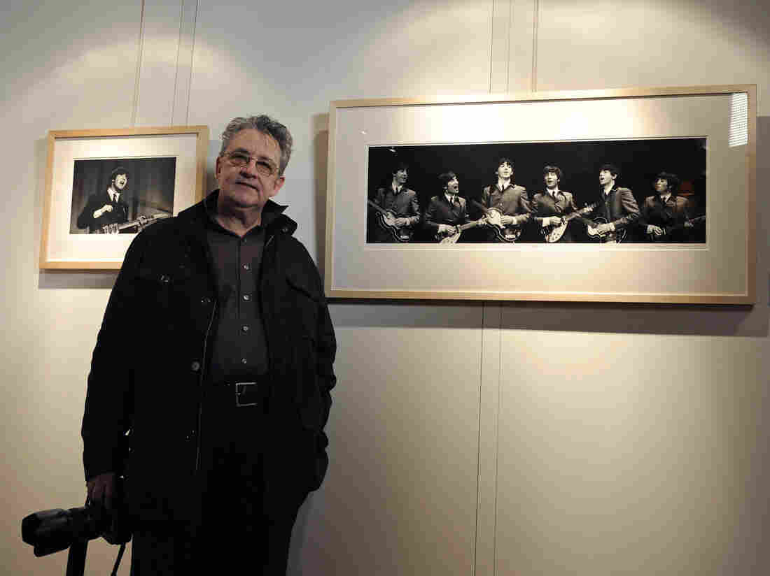 Photographer Mike Mitchell poses with his photographs of the first U.S. performance of The Beatles at the Washington Coliseum in central London in 2011.