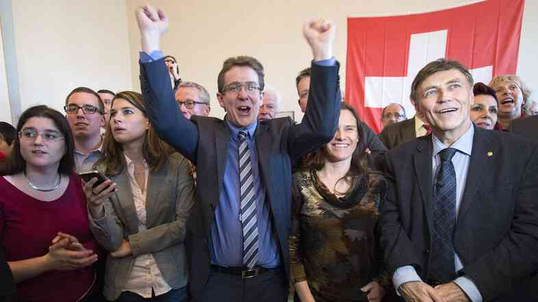 Members of the Swiss People's Party (SVP) cheer after the results after winning a narrow vote on an anti-immigration referendum on Sunday.
