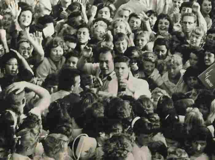 Laboe waves next to actor-musician Ricky Nelson (center, in the white blazer) amid a mob of fans in 1957.