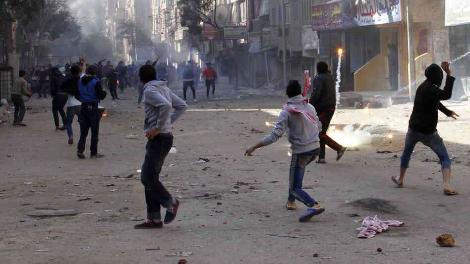 Supporters of the Muslim Brotherhood (background) clash with supporters of Egypt's army chief Abdel-Fatah el-Sissi in Cairo on Jan. 24.