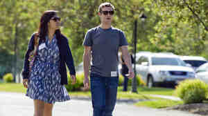 Mark Zuckerberg, president and CEO of Facebook, walks with Priscilla Chan in 2011.